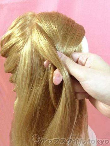 編み込みヘアアレンジの手順1の解説補助をしています。